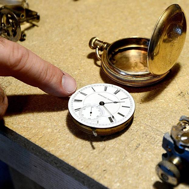 pocket watch being removed and cleaned