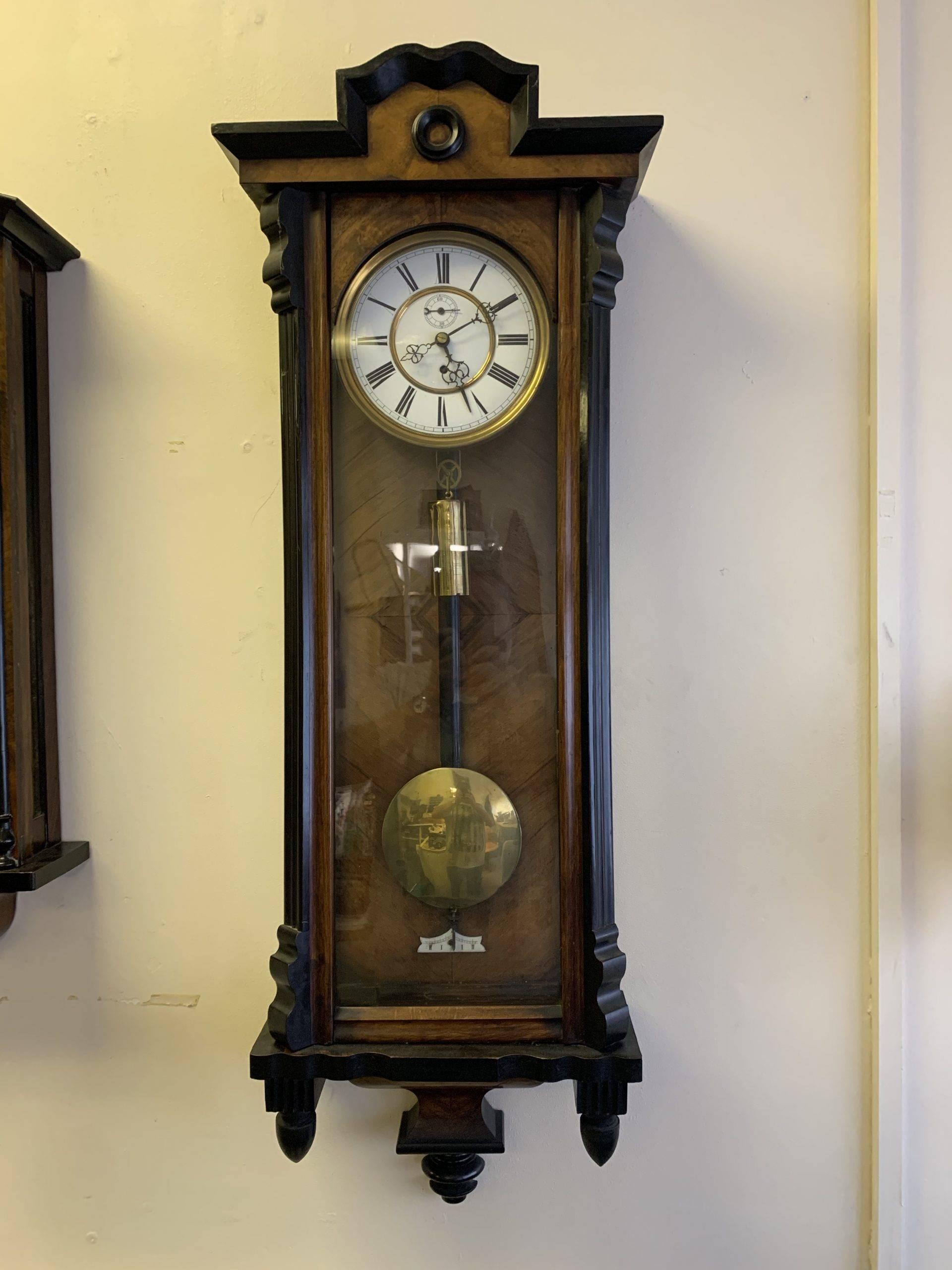 wall hanging clock with long golden pendulum