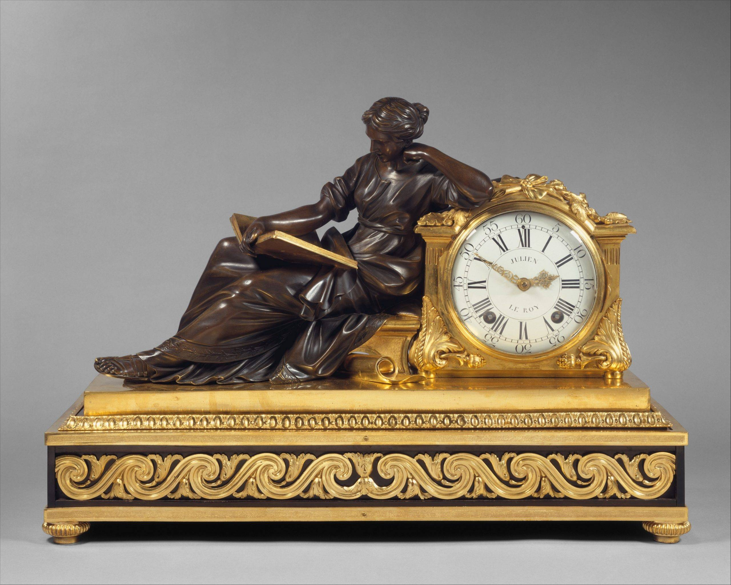 french mantel clock with woman reading book and gold design